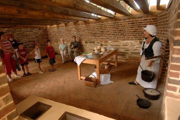 A small group of visitors listen to a guide in the kitchen at Poplar Forest, Thomas Jefferson's retreat home.